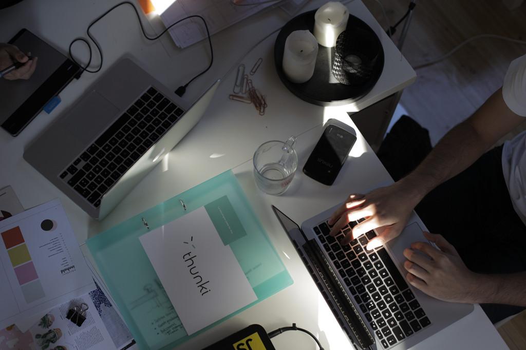 Bilde ovenfra på arbeidspultene våre der me har laptopper og arbeidspapirer strødd om kvarandre.